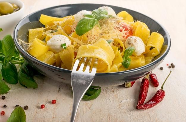 フォークに黄色の調理済みパスタパッパルデッレ、フェットチーネ、またはタリアテッレ。自家製リボンヌードルまたはマカロニとトマト、バジル、モッツァレラチーズのボール