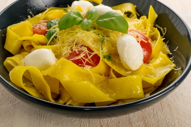 Yellow cooked pasta pappardelle, fettuccine or tagliatelle in black bowl. egg homemade ribbon noodles or macaroni with tomatoes, basil and mozzarella balls