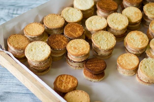 黄色いクッキーサンドイッチ。お菓子と木製トレイ。バニラカスタードを添えたサクサクのビスケット。家で美味しいペストリーを作ってください。