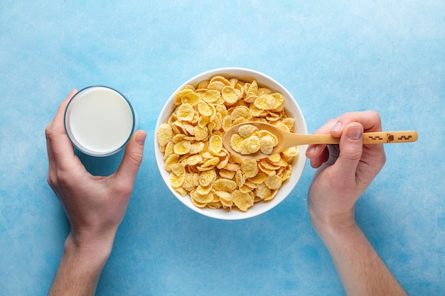 Yellow corn flakes and a glass of milk for dry breakfast. top view. cereals spoon and bowl