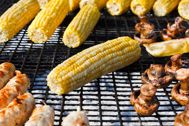 Yellow corncobs and mushrooms cooked at barbecue grill