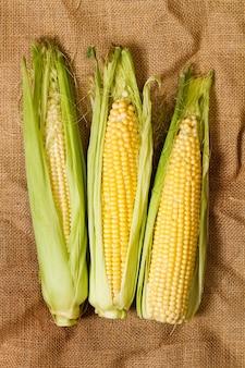 Желтые кукурузные початки с зелеными листьями на мешковине, вид сверху