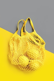 Yellow cotton net bag with lemons on grey background. colors of the year 2021 ultimate gray and illuminating. color trend palette. stylish background