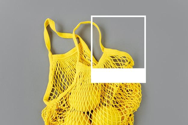 회색 배경에 레몬이 있는 노란색 면 그물 가방. 2021년 올해의 컬러 얼티밋 그레이와 일루미네이팅. 컬러 트렌드 팔레트. 세련된 배경