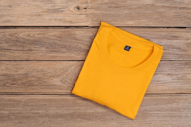 木製のテーブルに黄色い綿のtシャツ。