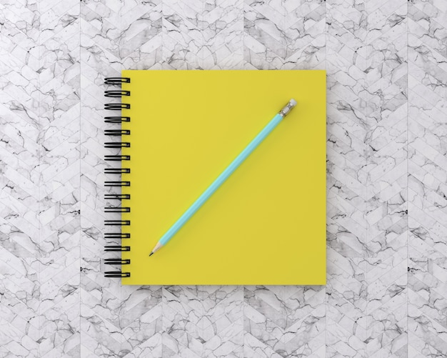Yellow cover notebook with blue pencil on marble background. minimal work space.