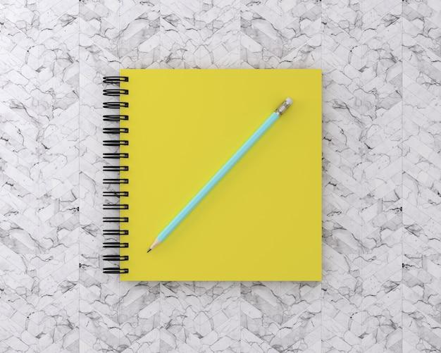 대리석 백그라운드에 파란색 연필로 노란색 표지 노트북. 최소한의 작업 공간.