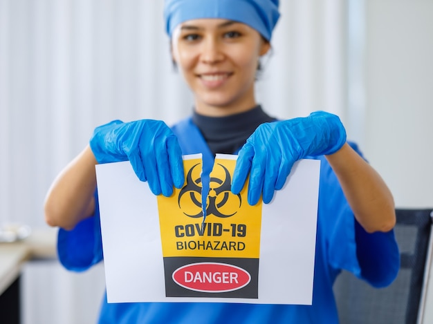 黄色のcovid-19バイオハザード危険紙の看板は、コロナウイルスのパンデミックが終了し、通常の生活が戻ったときに、ぼやけた背景の青い病院の制服を着た幸せな美しい医師によって引き裂かれました。