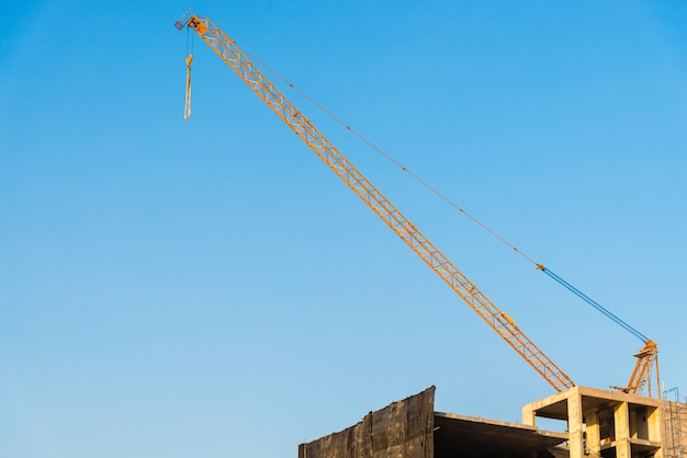 Yellow crane on building site with blue sky