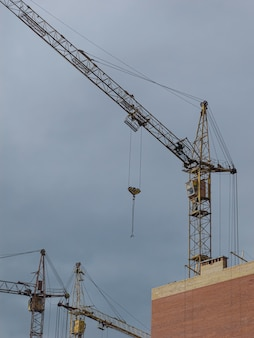 Yellow cranes on the background of buildings under construction