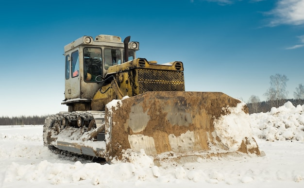 Yellow crawler tractor bulldozer with a bucket works in winter clearing the road from snow