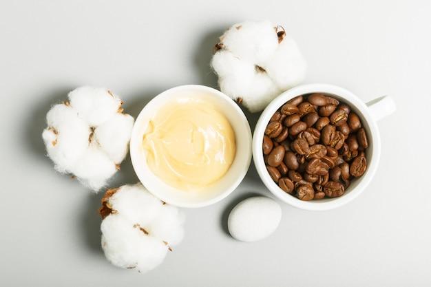 黄色のクリーム、コーヒーの穀物、灰色の背景に綿。自然派化粧品とパーソナルケアのコンセプト。平面図、フラットレイアウト。