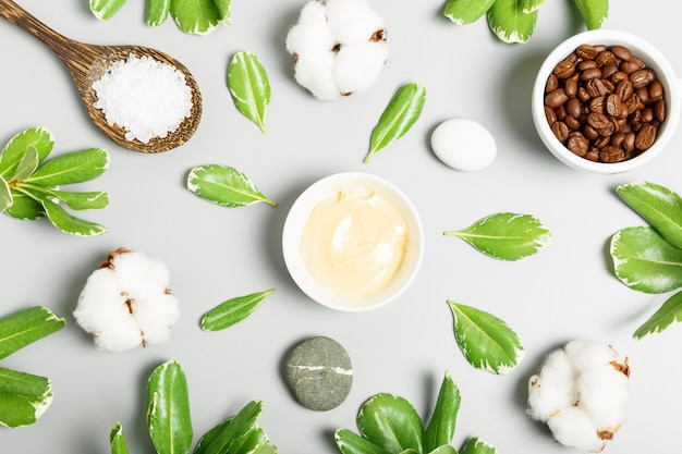 Yellow cream, coffee grains, cotton, bath salt and green leaves on a gray background. natural cosmetics and spa concept. top view, flat lay.