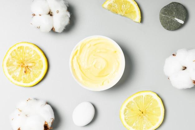 黄色のクリーム、レモン、灰色の背景に綿。自然派化粧品と美容のコンセプトです。平面図、フラットレイアウト。