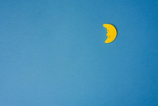 青い夜空に対して黄色の三日月。右側の申請用紙。