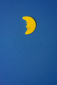 Yellow crescent moon against blue night sky. application paper on the right. copy space