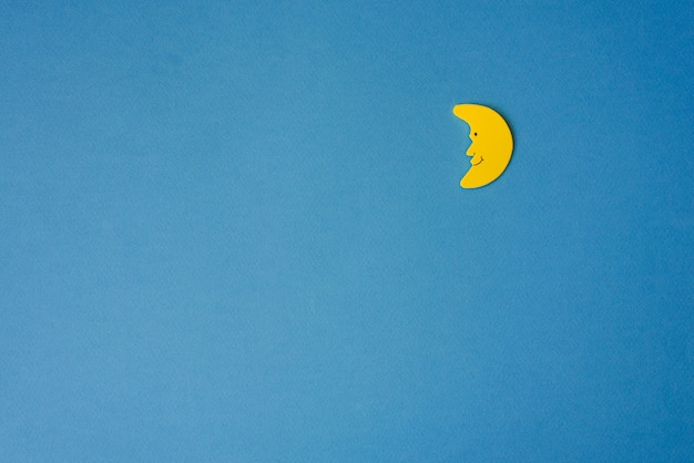 Yellow crescent moon against blue night sky. application paper on the right.