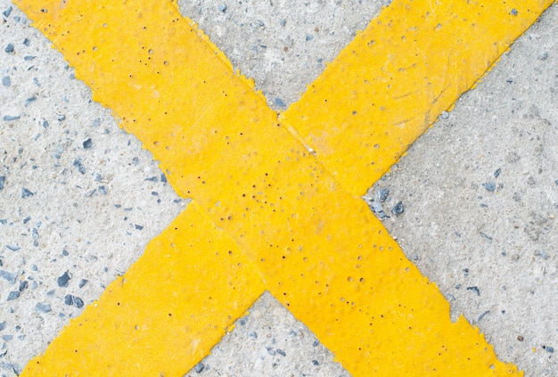 Yellow cross symbol on the road