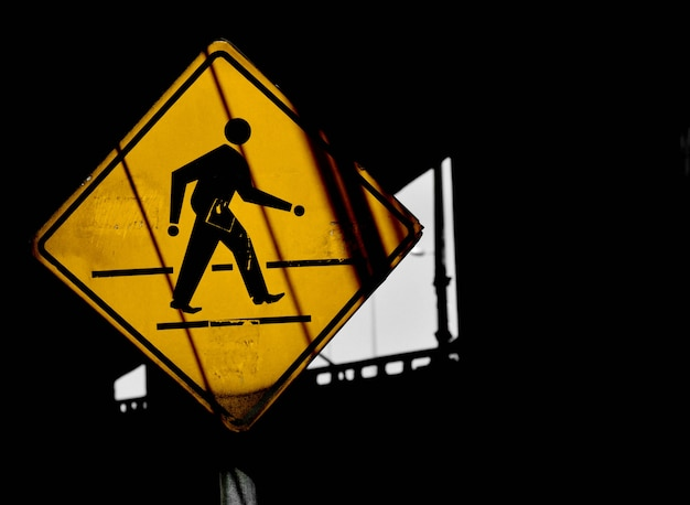 Yellow crosswalk sign with shadow in urban