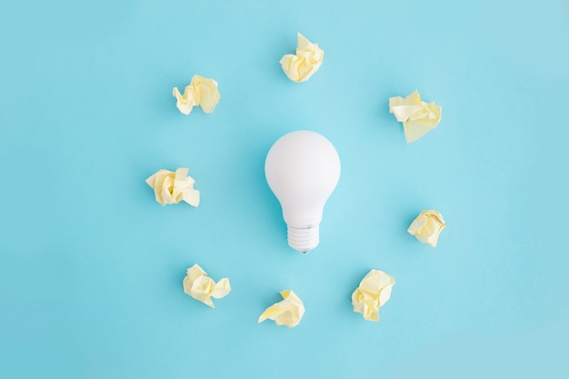 Yellow crumpled paper around the white light bulb on blue background