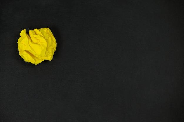 Желтый мятый бумажный шарик на черном фоне