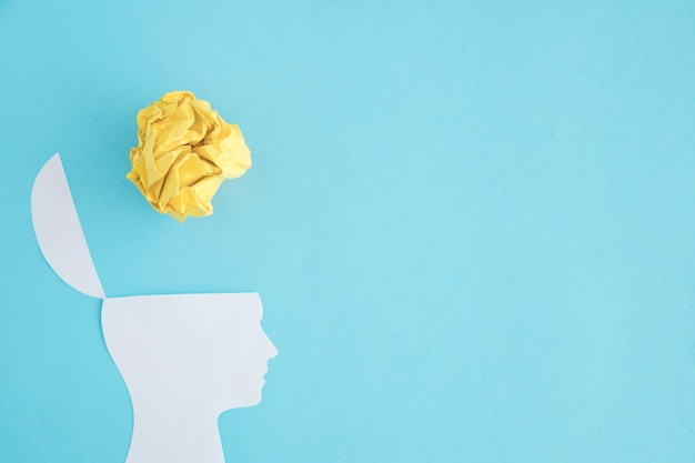 Yellow crumpled paper ball over the open head on blue backdrop