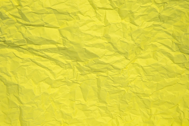 Yellow crumpled paper close up texture background.