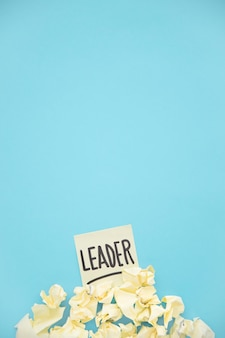 Yellow crumpled paper on leader sticky note over the blue background
