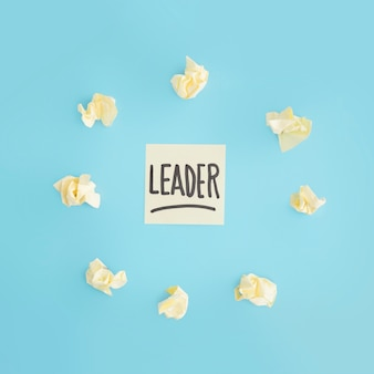 Yellow crumpled paper surrounded around leader text adhesive note on blue backdrop