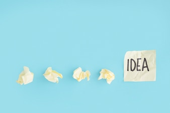 Yellow crumpled papers with idea text on the sticky note over the blue background