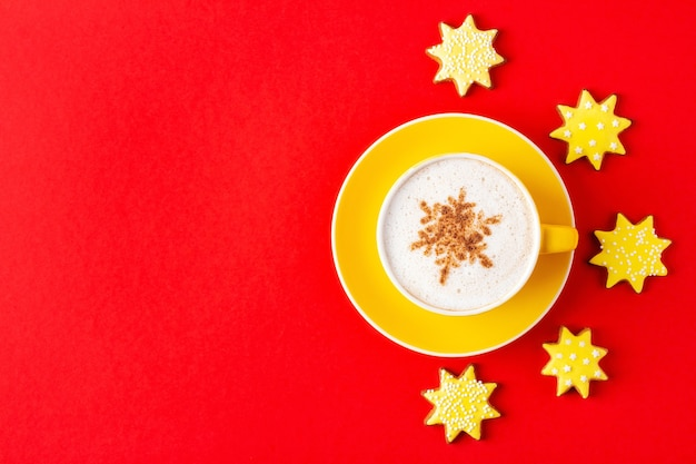 Yellow cup of christmas cappuccino on saucer and star shaped cookies on red background, flat lay. holiday coffee with sweet treat.