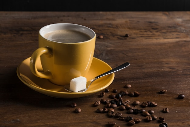 Yellow cup of coffee and plate with sugar cube
