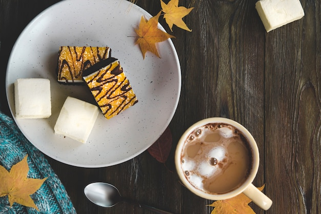 Yellow cup of coffee with marshmallows and orange dessert on a white plate flat lay.