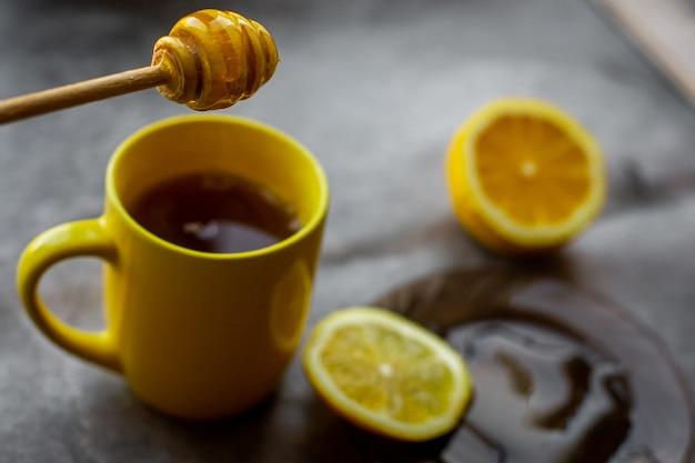 黄色いカップ、受け皿に蜂蜜を滴下、レモンと灰色の背景