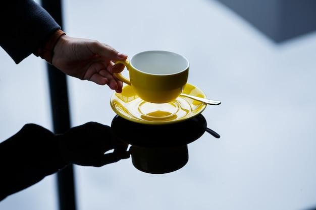ガラスのテーブルの背景に女の子の手に受け皿とコーヒーやお茶の黄色いカップ。