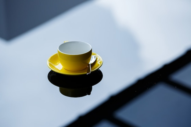 Желтая чашка для кофе или чая с блюдцем на стеклянном столе.