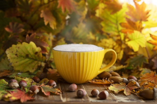 Желтая чашка капучино в осенней листве с желудями и орехами. осенняя атмосфера.
