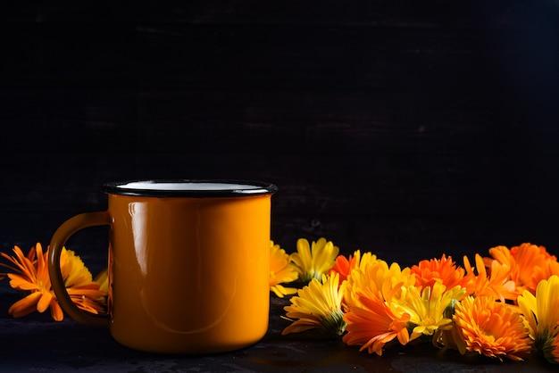 노란색 달리아로 둘러싸인 노란색 컵 커피