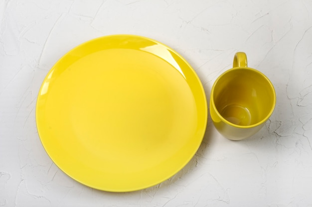 Yellow cup and plate in a fashionable color, on a white background.