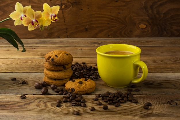 Yellow cup of strong coffee and coffee beans, copy space