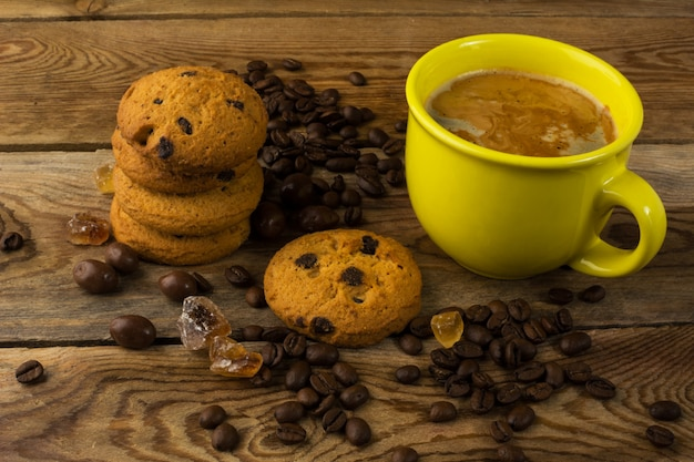 Yellow cup of strong coffee and cookies