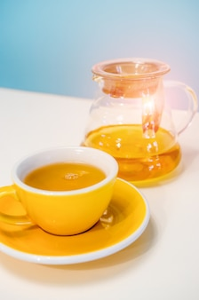 Yellow cup of tea and glass teapot on the table. blue background