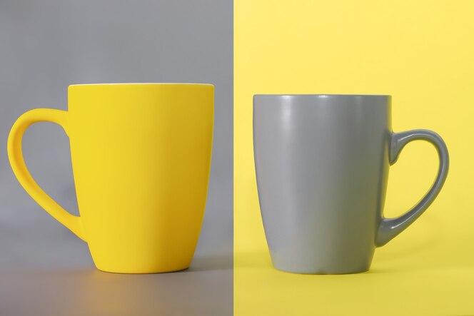 在终极灰色表面和灰色杯子的黄色杯子在黄色桌上。2021年的颜色。照亮和终极灰色。
