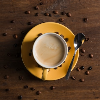 Yellow cup with beverage near coffee beans