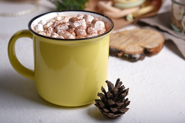 Желтая чашка с какао, украшенная зефиром крупным планом, зефир на заднем плане