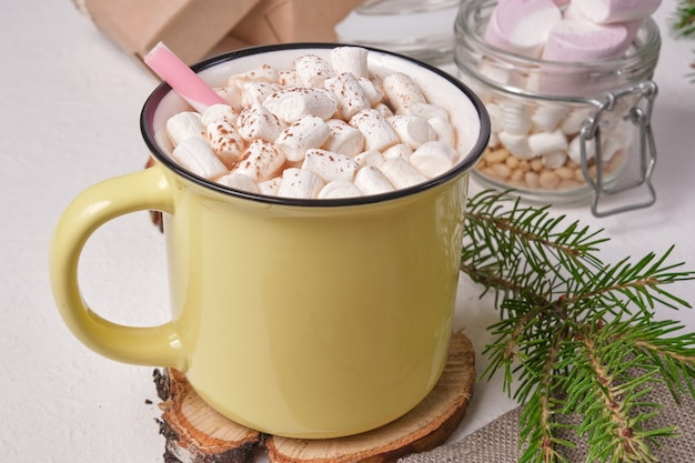 のこぎりで切った木で作られたスタンドにマシュマロで飾られたコカオの黄色いカップ、マシュマロの瓶、トウヒの枝、背景にクリスマスプレゼント