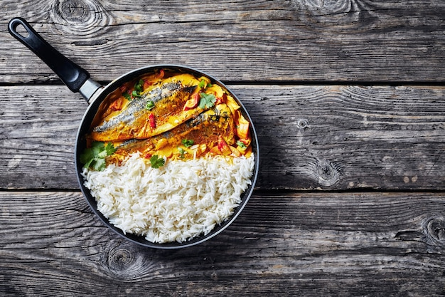 Yellow curry, panang curry with grilled saba mackerel fish served with steamed long grain rice in a skillet on a rustic wooden table, view from above, flatlay, empty space
