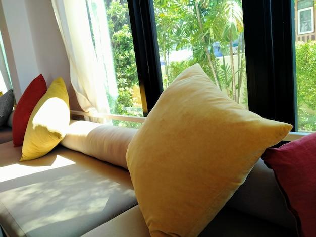 背景に庭のある快適なソファの黄色いクッション