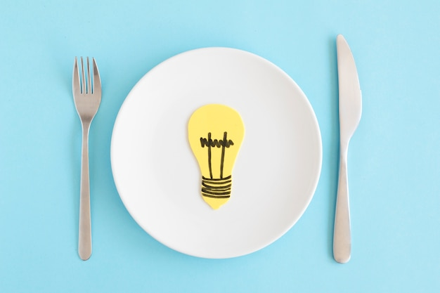 Yellow cutout light bulb on white plate with fork and butter knife against blue background