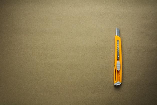 갈색 재활용 된 종이-배경에 노란색 커터